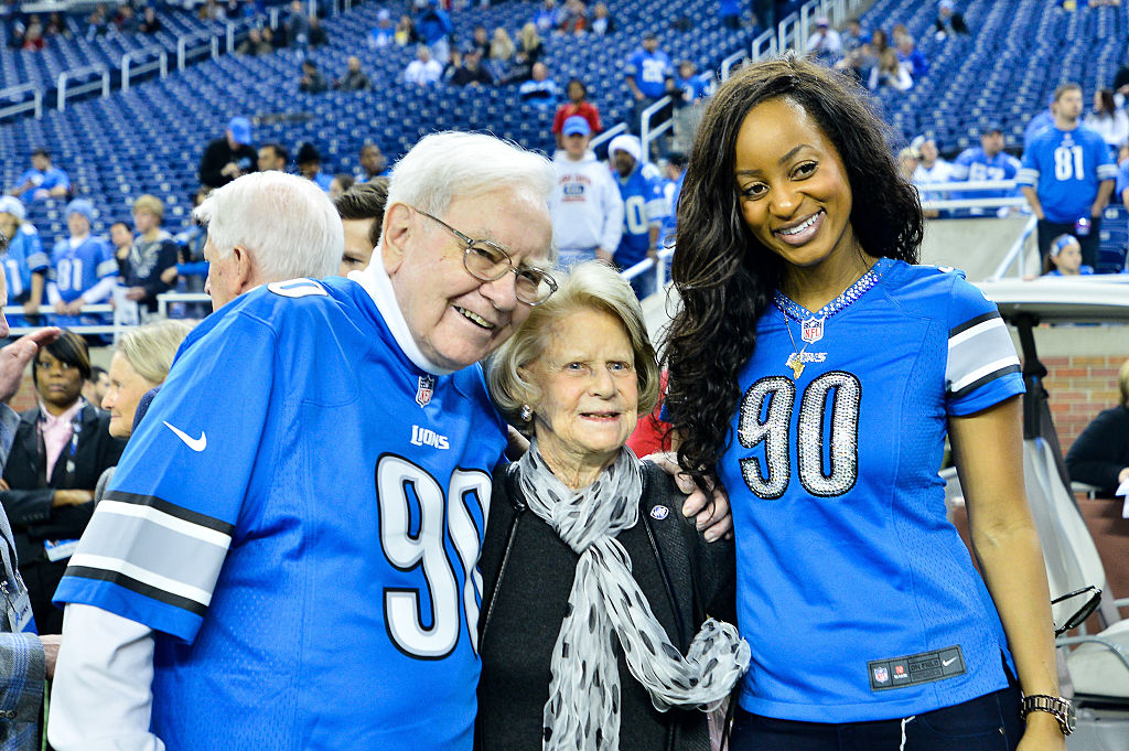 Warren Buffett and Mrs. Martha Ford talk with Odette Ngum Suh during the pre-game warmups