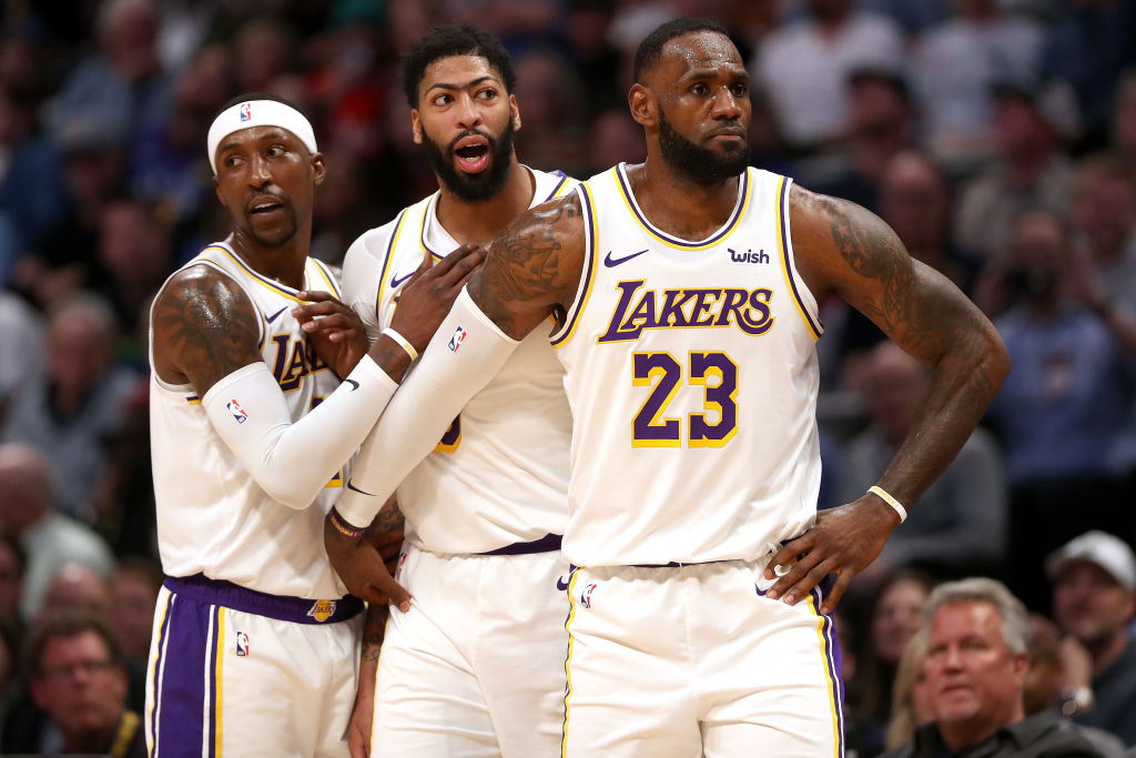 Anthony Davis of the Los Angeles Lakers is restrained by Kentavious Caldwell-Pope and Lebron James