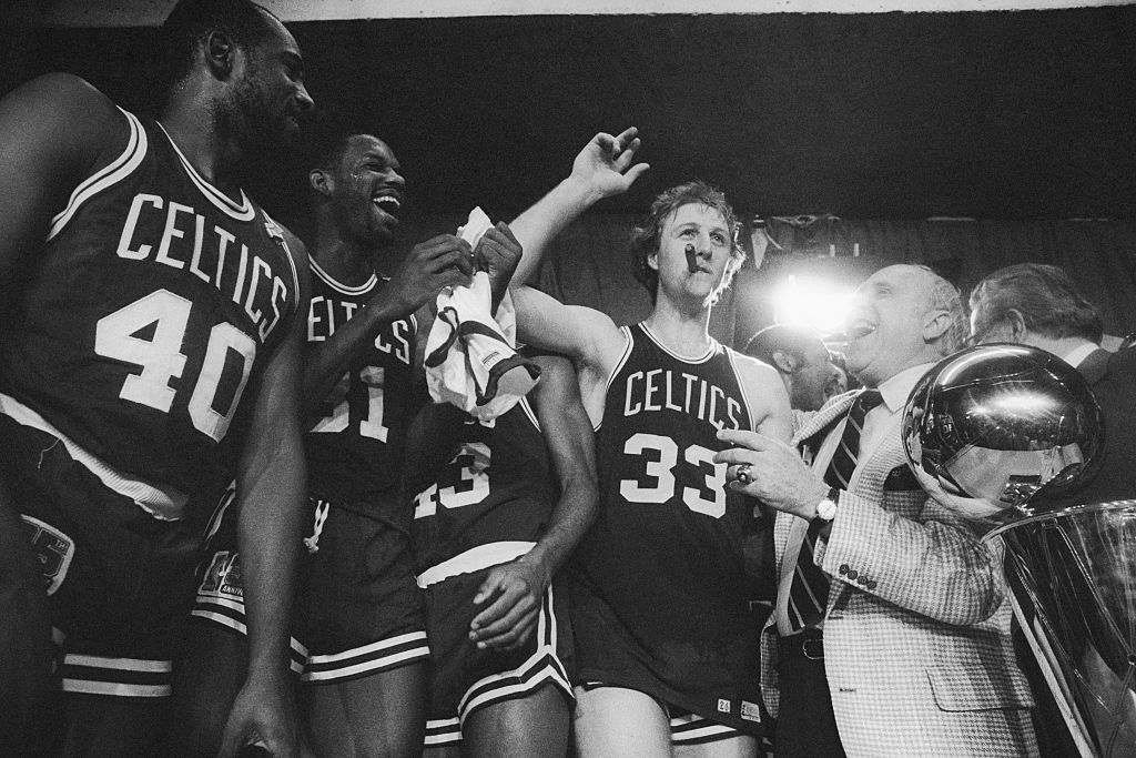 Boston Celtics general manager Red Auerbach laughs after Larry Bird stole his cigar during a victory celebration, after the Celtics won the NBA championship.