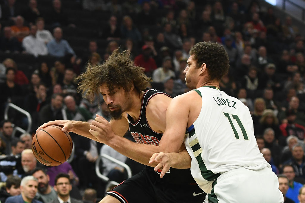 Robin Lopez of the Chicago Bulls drives around Brook Lopez of the Milwaukee Bucks