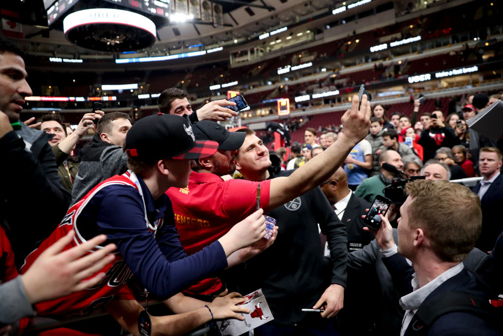 The Denver Nuggets' Nikola Jokic takes photos with fans after a win