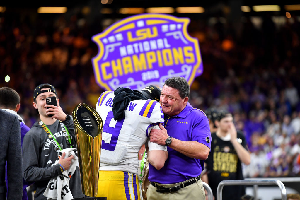 Head coach Ed Orgeron of the LSU Tigers and Joe Burrow hug on the championship stage