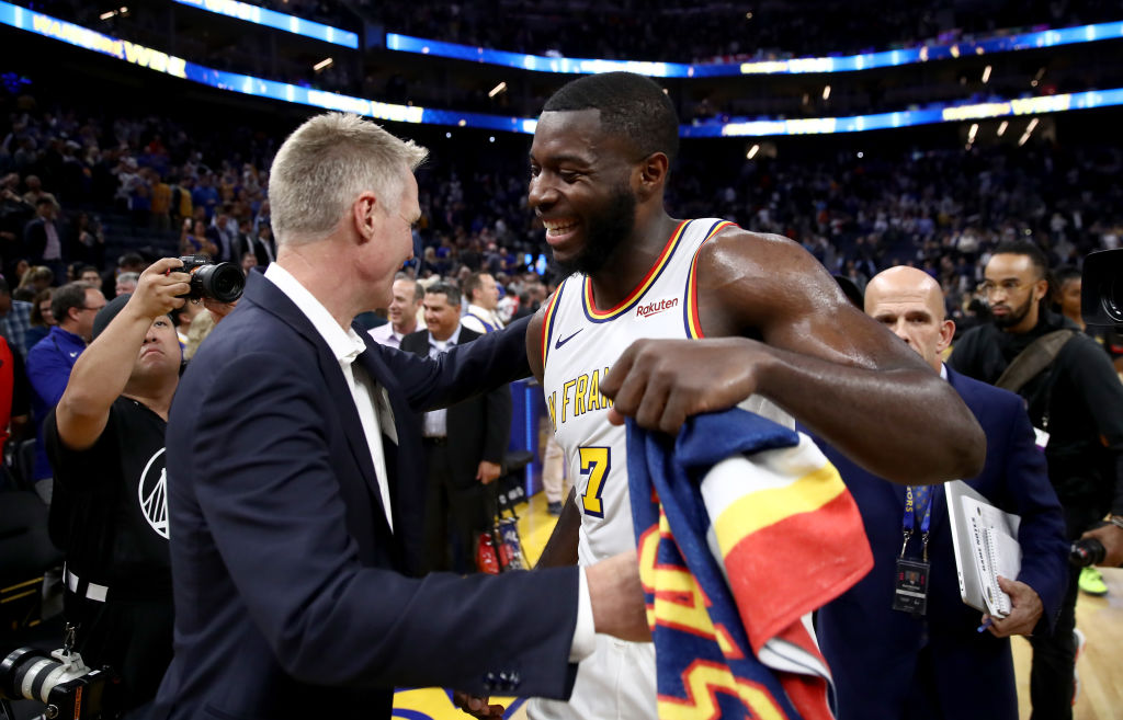 Eric Paschall of the Golden State Warriors is congratulated by head coach Steve Kerr