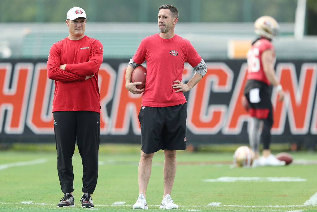 Head coach Kyle Shanahan of the San Francisco 49ers talks with general manager John Lynch