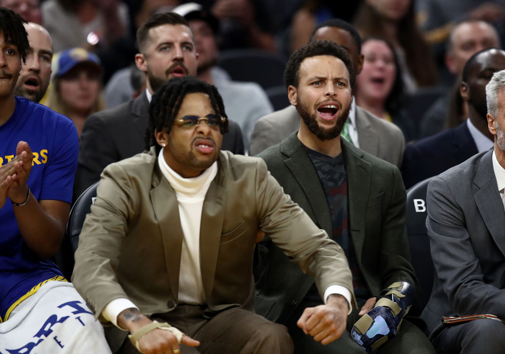 Injured players D'Angelo Russell (L) and Stephen Curry of the Golden State Warriors react on the bench