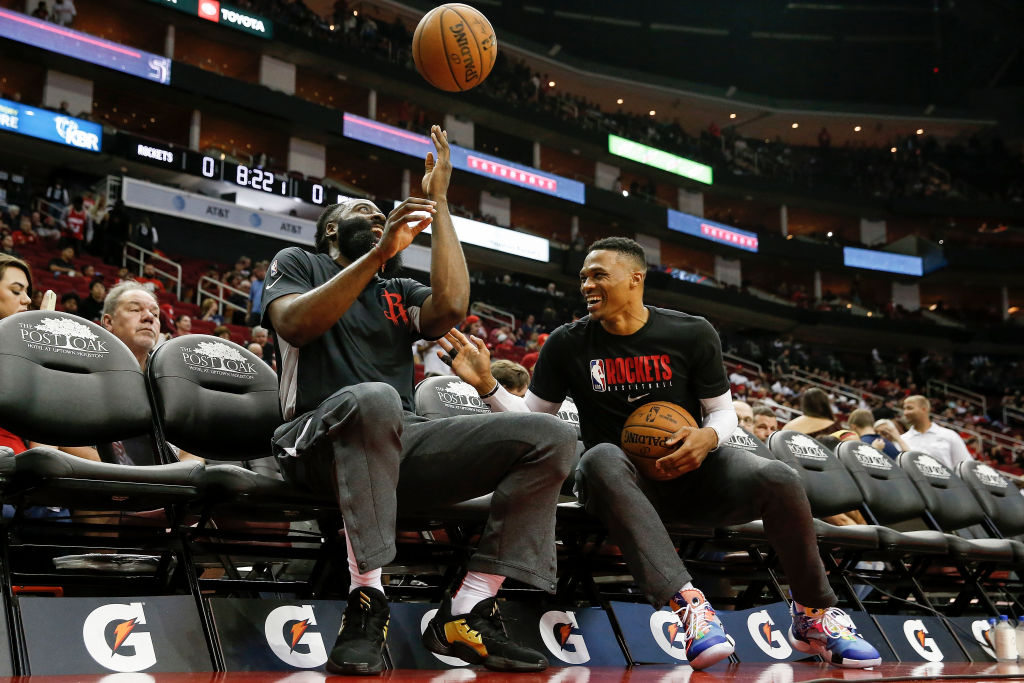James Harden of the Houston Rockets and Russell Westbrook sit on the bench