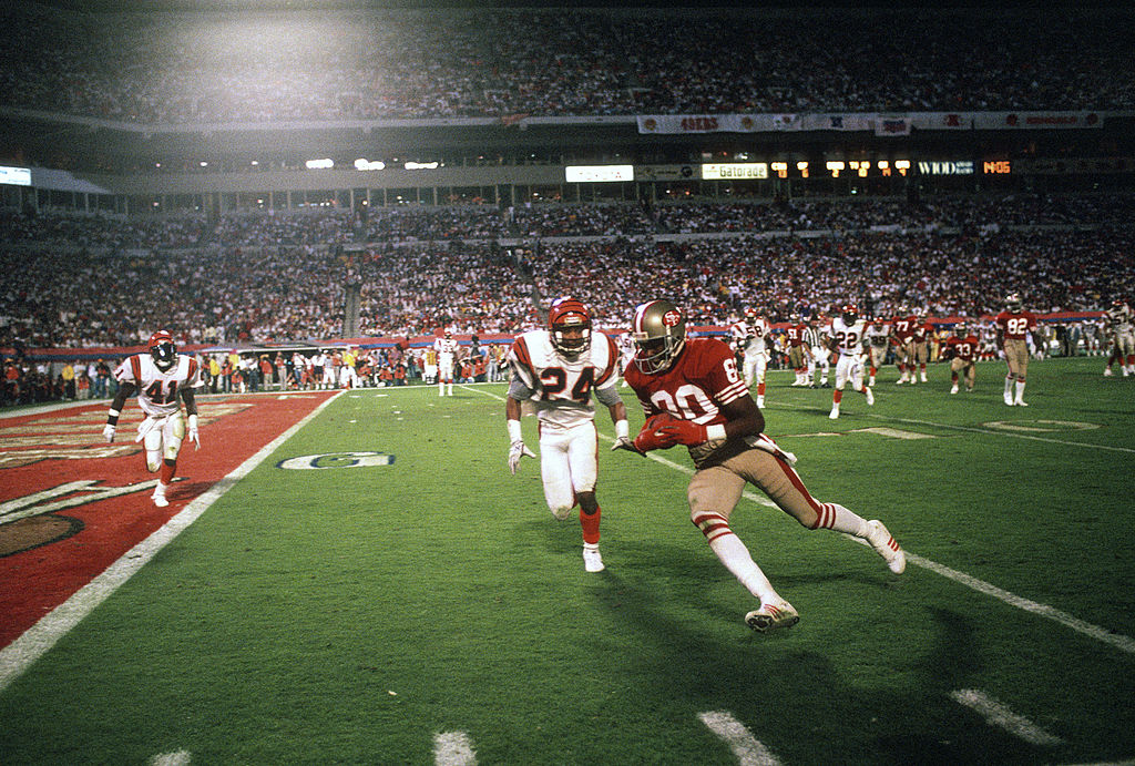 Jerry Rice of the San Francisco 49ers runs with the ball toward the end zone while pursued by Lewis Billups of the Cincinnati Bengals during Super Bowl XXIII