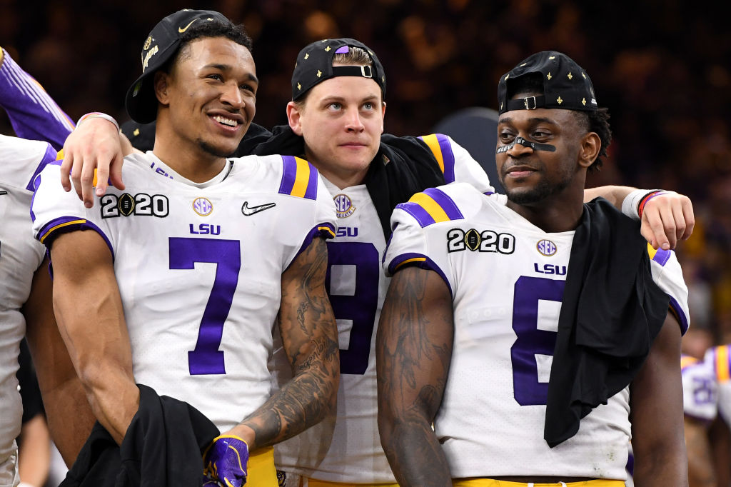 Grant Delpit, Joe Burrow, and Patrick Queen of the LSU Tigers celebrate after winning the College Football Playoff National Championship