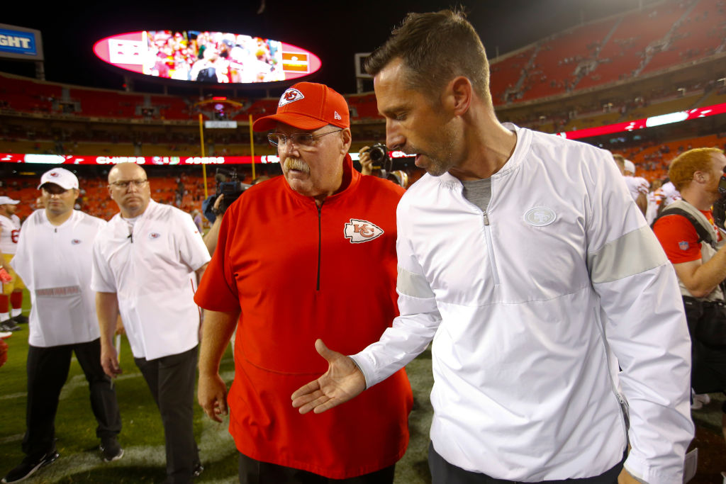 Head Coach Andy Reid of the Chiefs and Head Coach Kyle Shanahan of the 49ers talk on the field