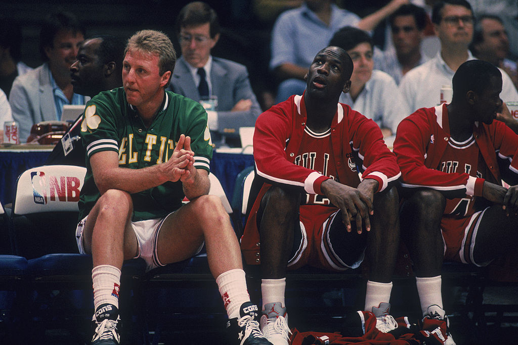 Larry Bird of the Boston Celtics and Michael Jordan of the Chicago Bulls sit on a bench during the 1990 NBA All-Star game