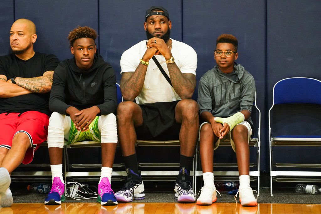 (L-R) LeBron James Jr., LeBron James Sr., and Bryce Maximus James watch Zaire Wade's AAU game in 2018