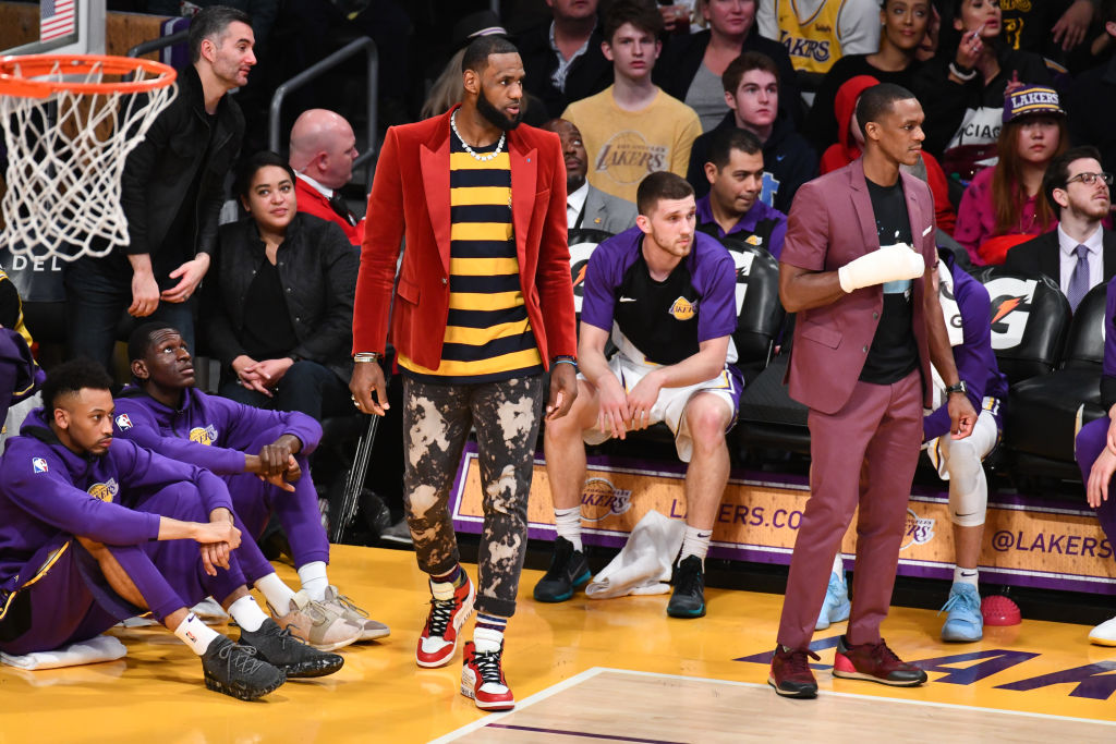 LeBron James, benched with a groin injury, cheers on his teammates while wearing a suit and necklace