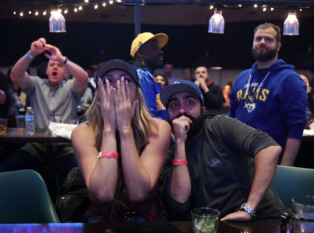 Los Angeles Rams fans Ella Silver (L) and Moe Helmy react to Super Bowl LIII