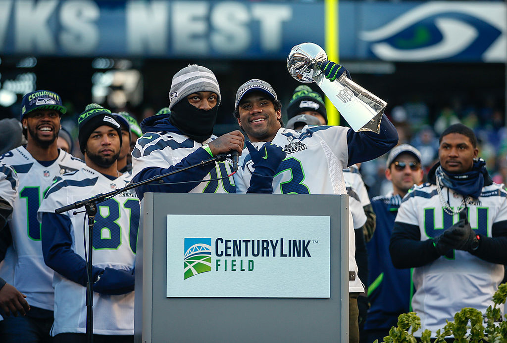 Quarterback Russell Wilson of the Seattle Seahawks holds the Lombardi Trophy as running back Marshawn Lynch looks on in 2014