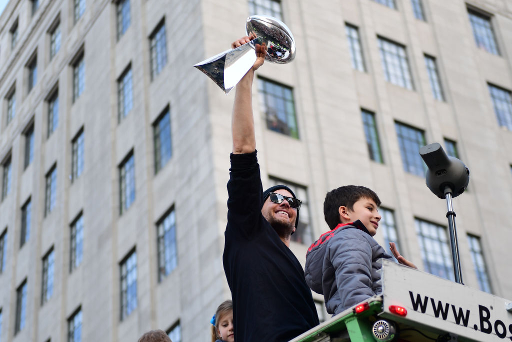 Tom Brady of the New England Patriots displays the Vince Lombardi trophy during the Super Bowl Victory Parade in 2019