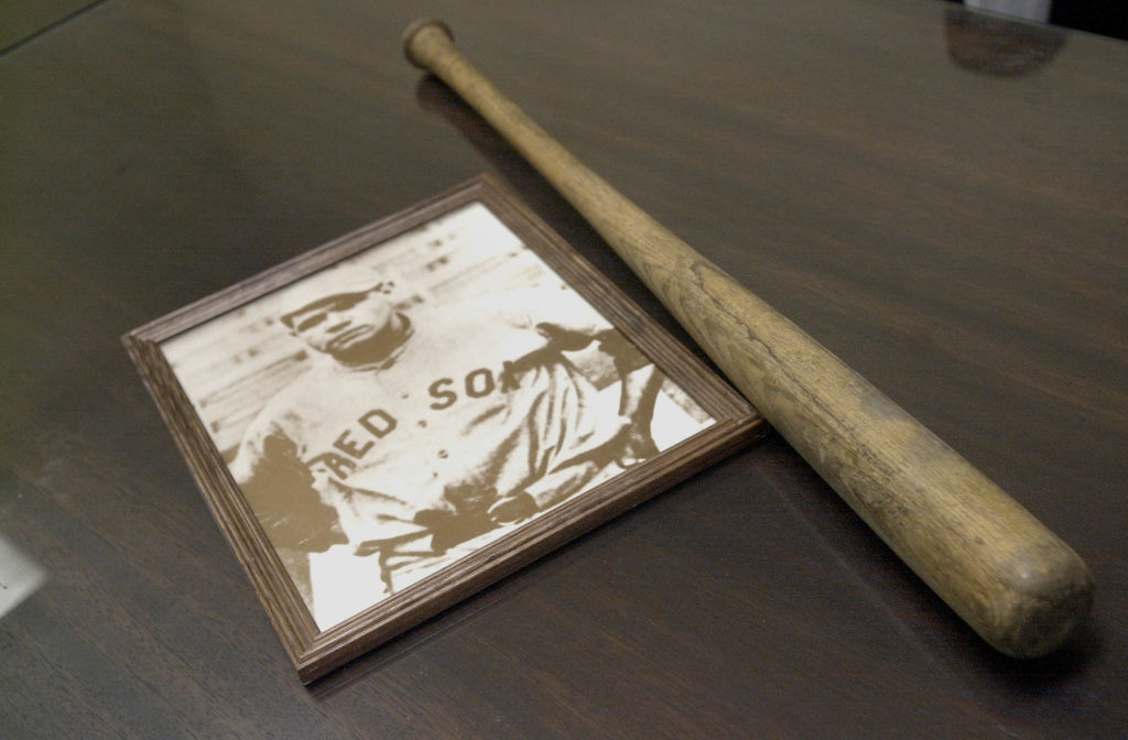 A vintage photo of baseball player Babe Ruth sits on a table next to a wooden practice bat he used to use.