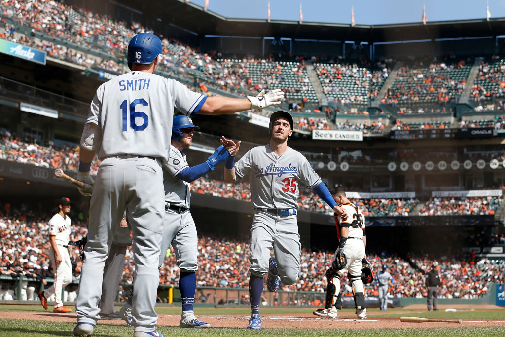 Cody Bellinger and Max Muncy of the Los Angeles Dodgers celebrate with teammate Will Smith