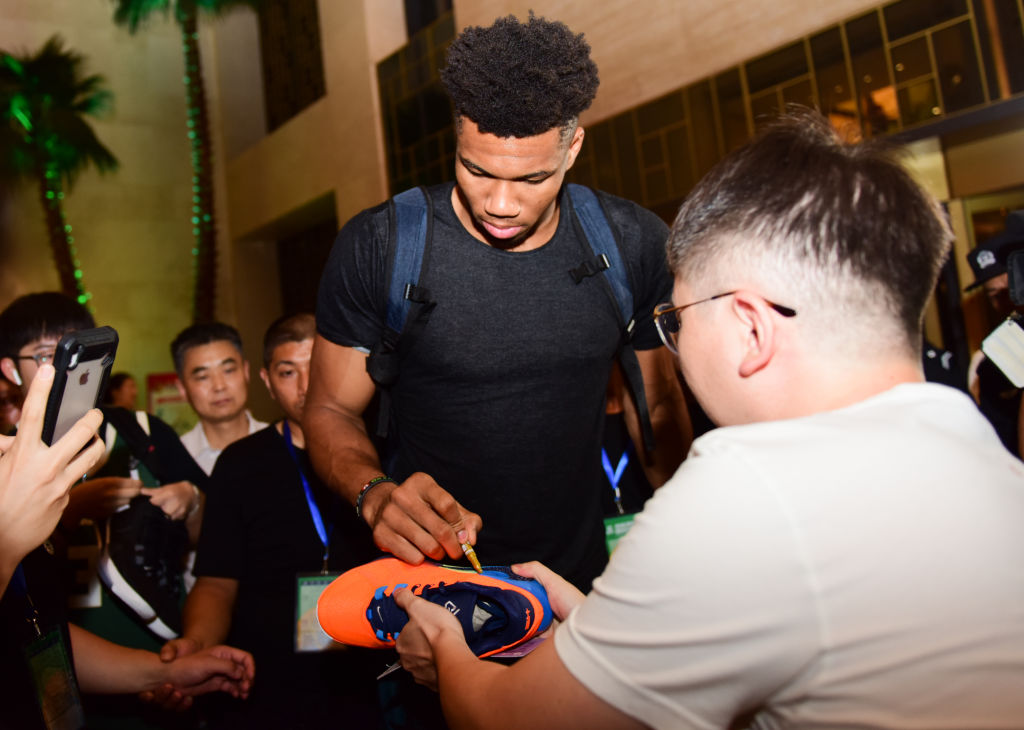 Greek-Nigerian basketball player Giannis Antetokounmpo signs a bright orange sneaker for a fan in a crowd.