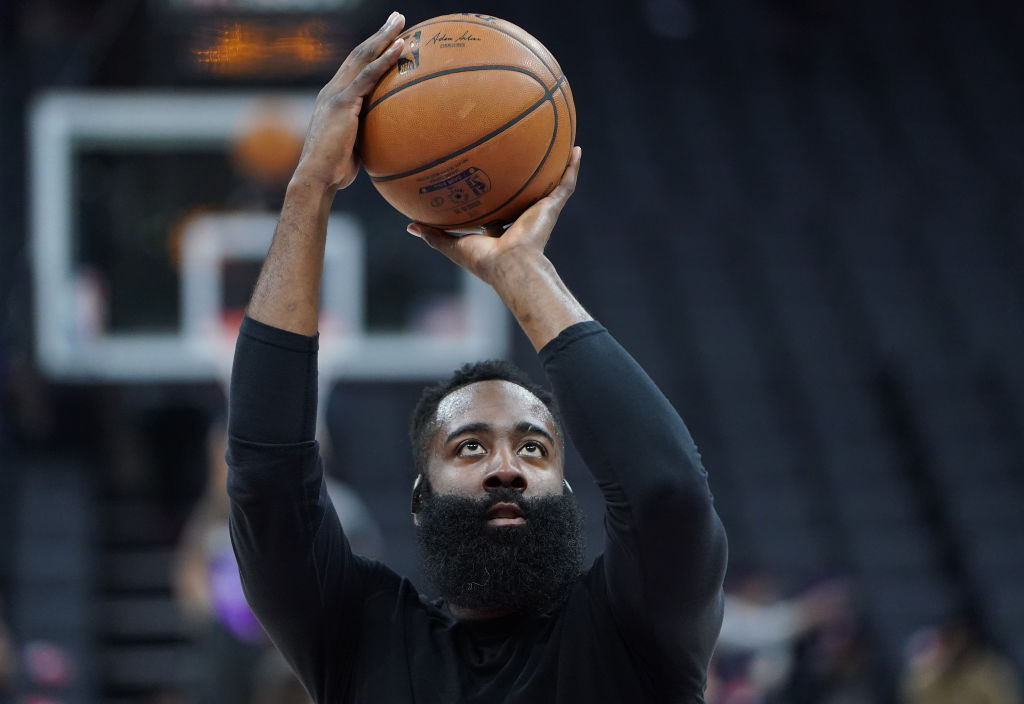 Basketball player James Harden of the Houston Rockets holds a ball over his head as he prepares to make a free throw while warming up.