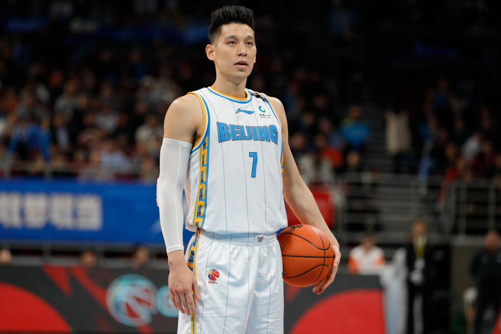 Basketball player Jeremy Lin stands during a game holding the ball at his side.