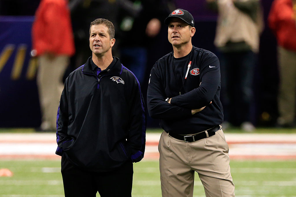 John and Jim Harbaugh standing at midfield before a game