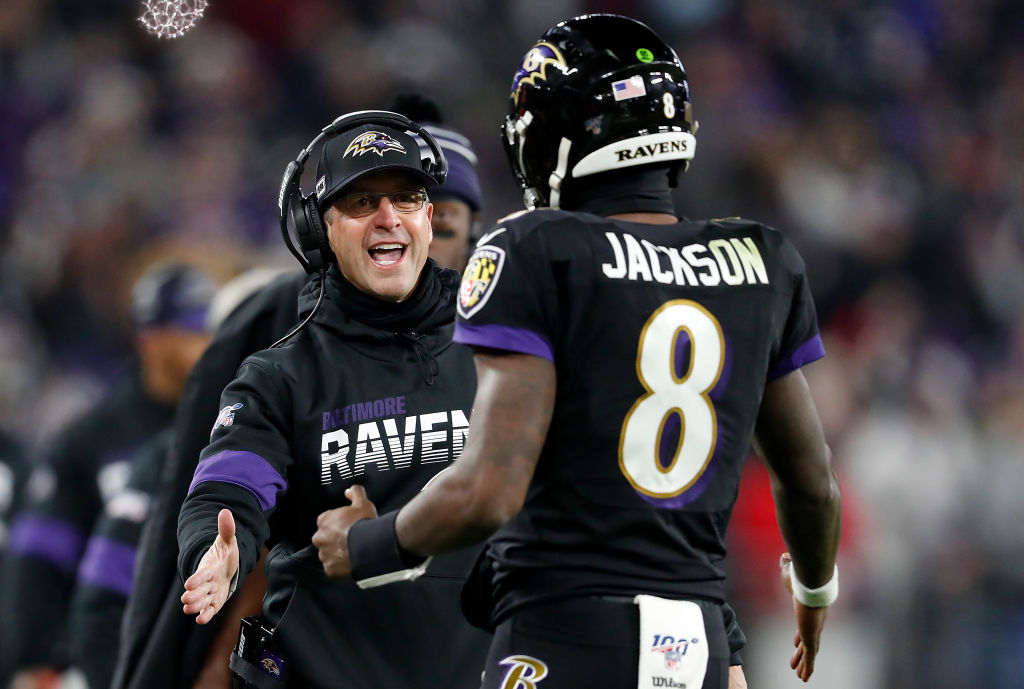 Coach John Harbaugh and Lamar Jackson talk on the sideline during an NFL game