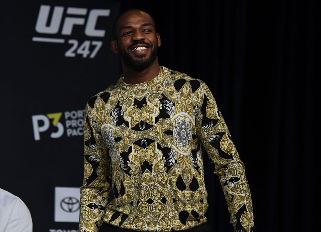 UFC fighter Jon Jones smiling on stage at a press conference.