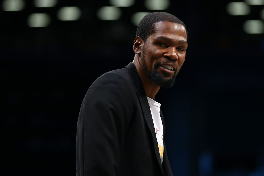 Kevin Durant watches a Nets game from the sideline