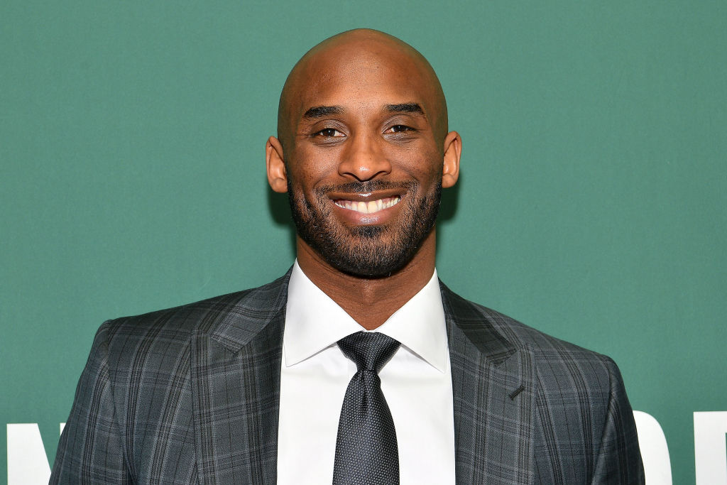 Kobe Bryant smiling while wearing a suit at a book signing event.