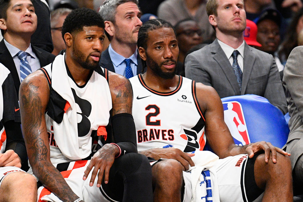 Los Angeles Clippers guard Paul George and forward Kawhi Leonard sit on the bench