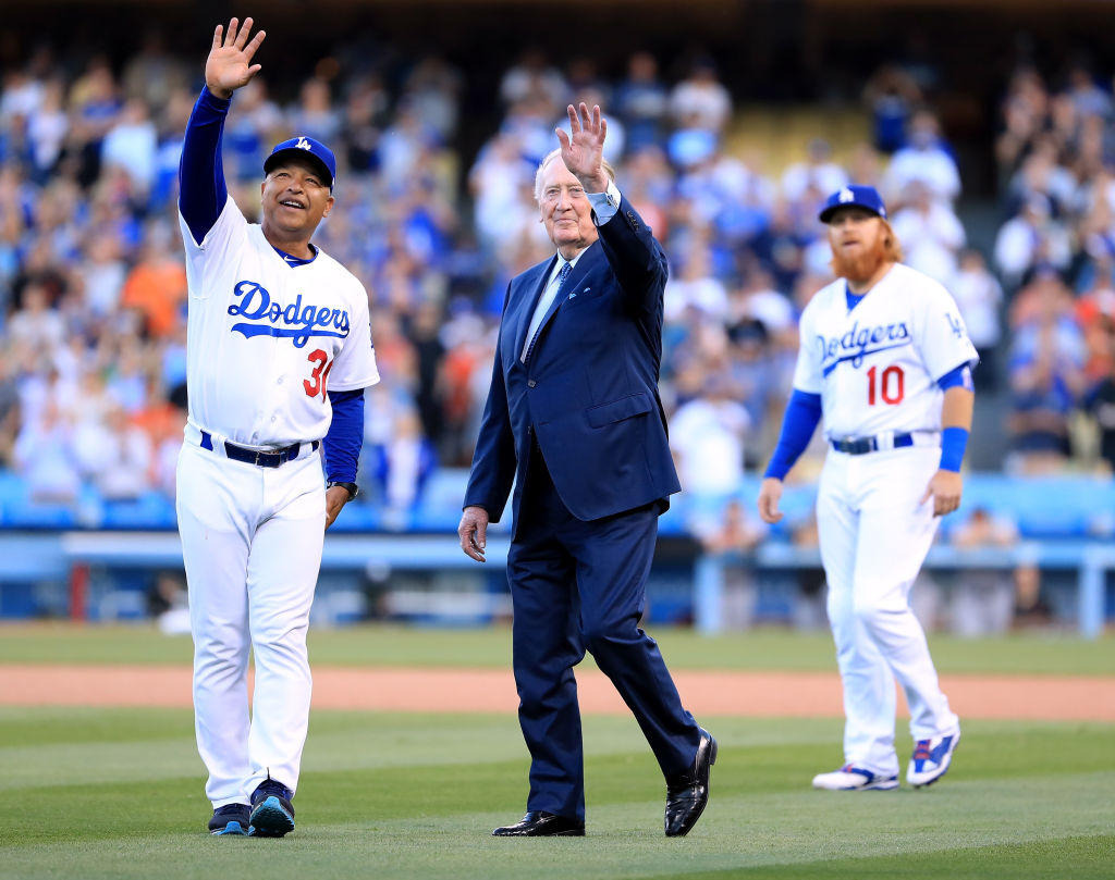 Los Angeles Dodgers manager Dave Roberts and announcer Vin Scully wave to fans