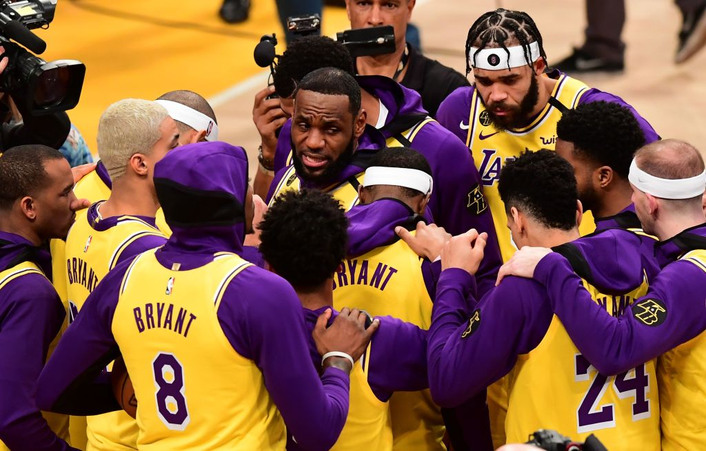 Los Angeles Lakers player LeBron James speaks with teammates as they wear jerseys with NBA legend Kobe Bryant's numbers