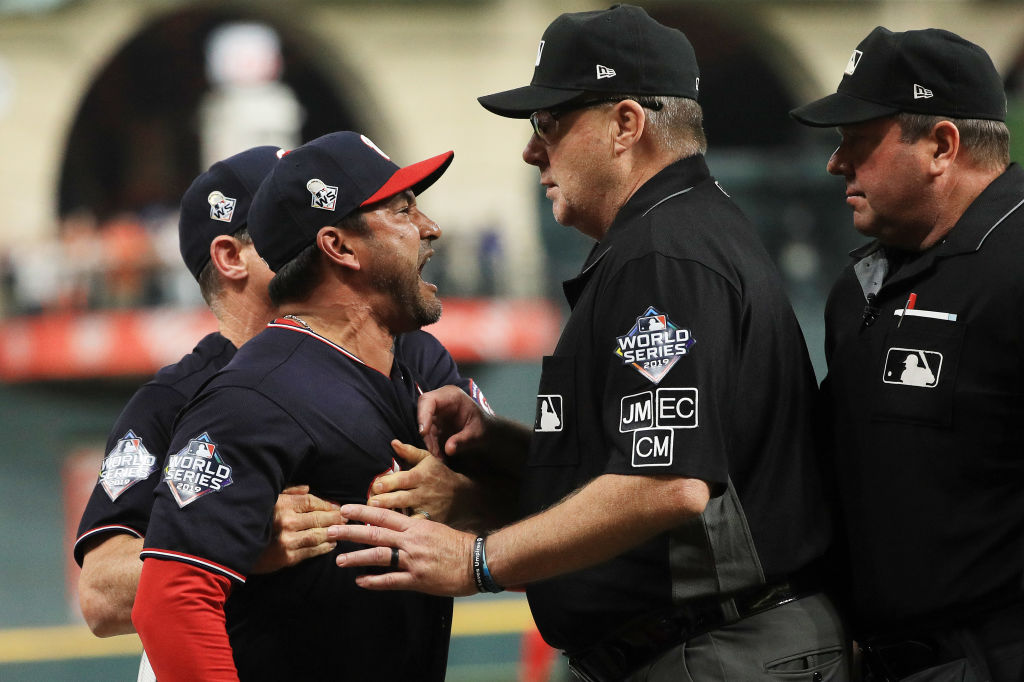 MLB umpires argue with a manager during a game