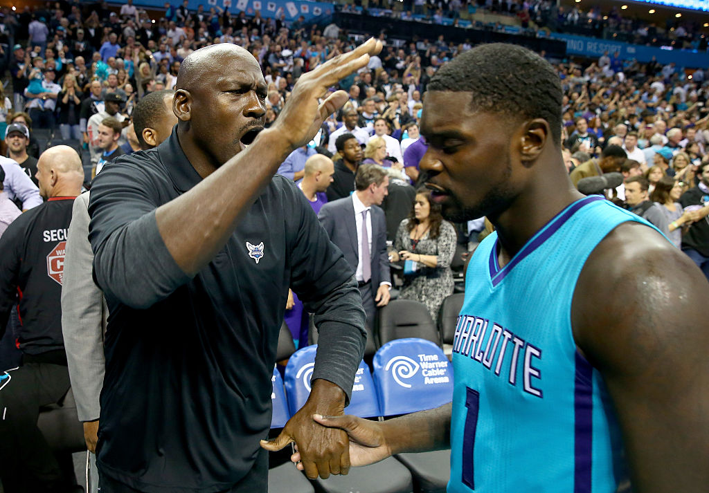 Charlotte Hornets owner Michael Jordan celebrating with a player