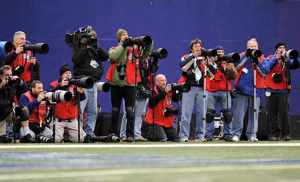 NFL photographers lined up on the sideline of a game