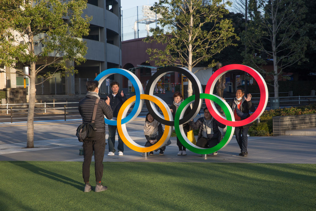 A man takes a photo of people posing behind the Olympic Rings near the New National Stadium in Tokyo.
