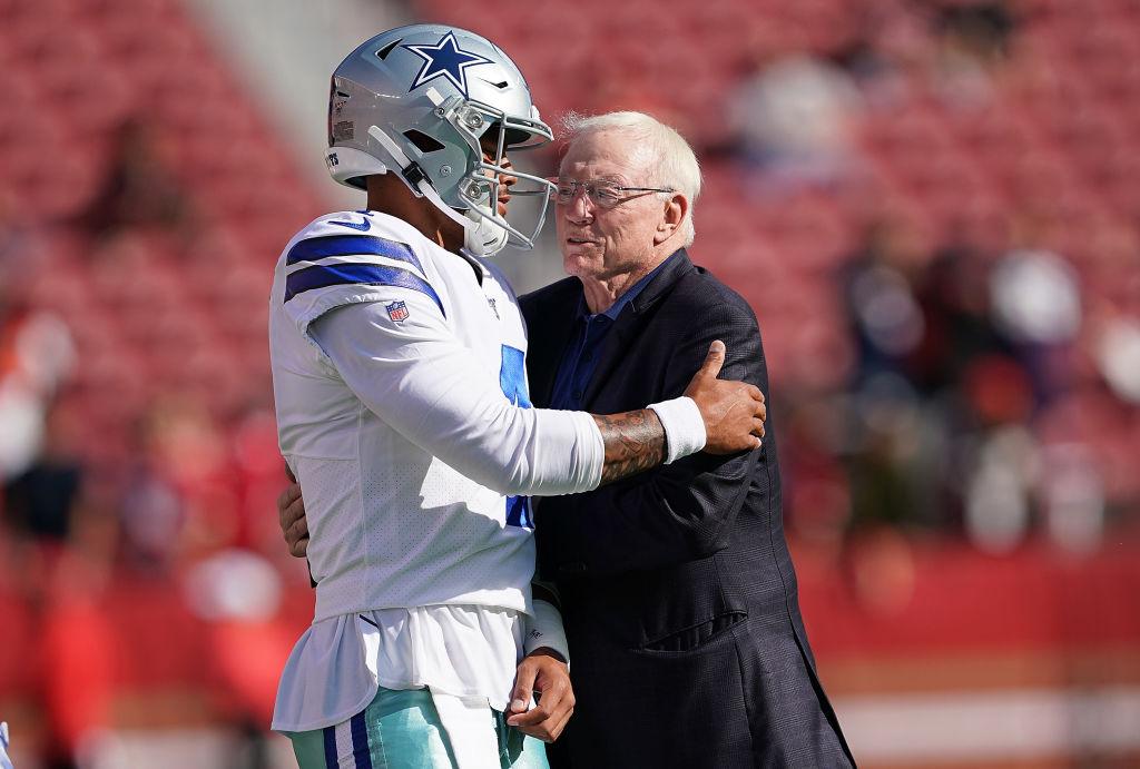 Quarterback Dak Prescott and team owner Jerry Jones of the Dallas Cowboys hug each other