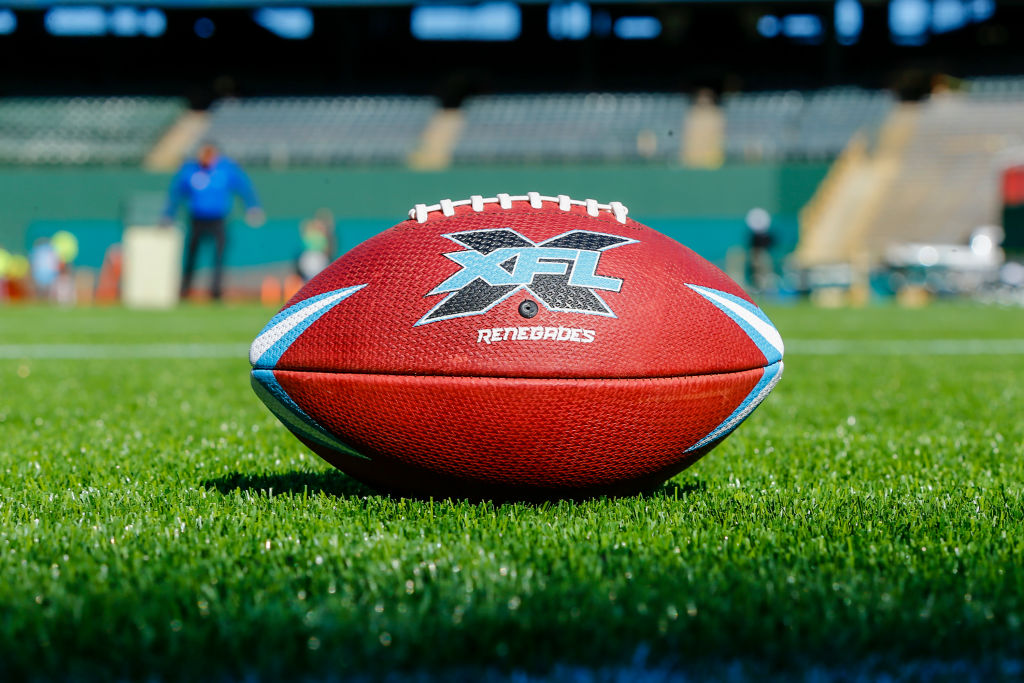 An XFL football laying on a field during practice
