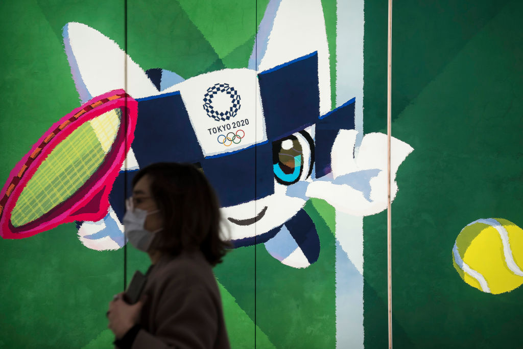 A pedestrian wearing a face mask walks past a display with an illustration of the 2020 Tokyo Olympic and Paralympic Games mascot Miraitowa