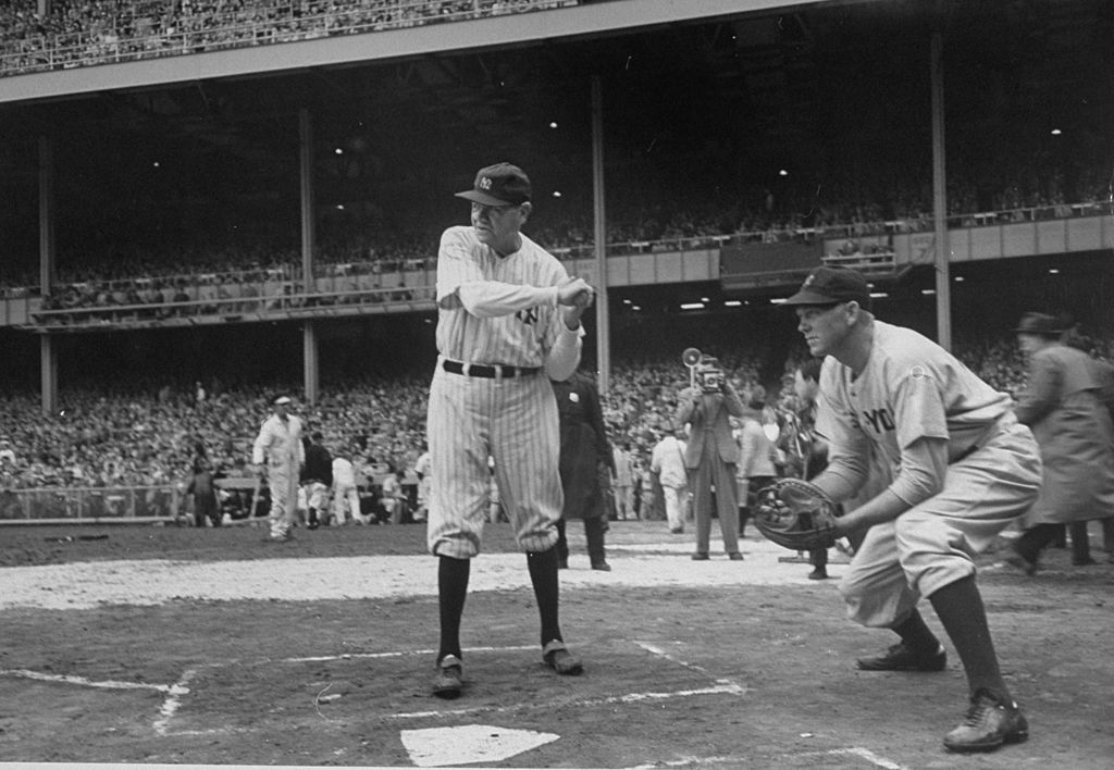 Babe Ruth (L) taking a practice hit at the New York Yankee's 25th anniversary