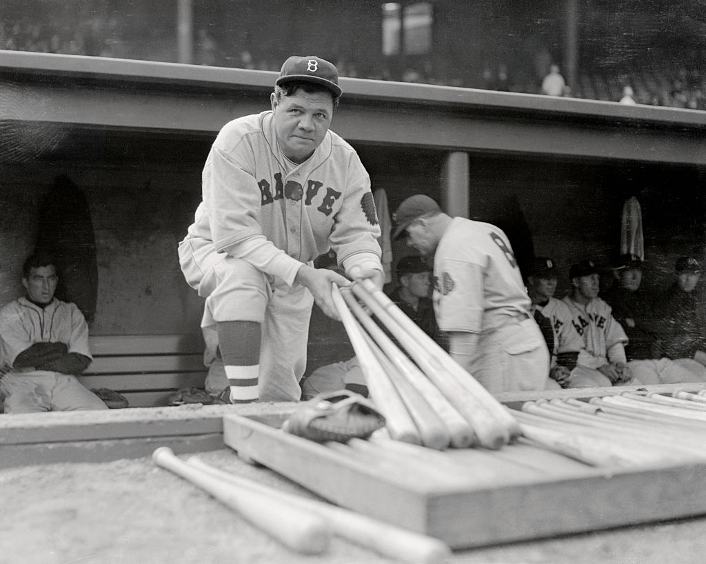 Baseball Player Babe Ruth holds several baseball bats during a game