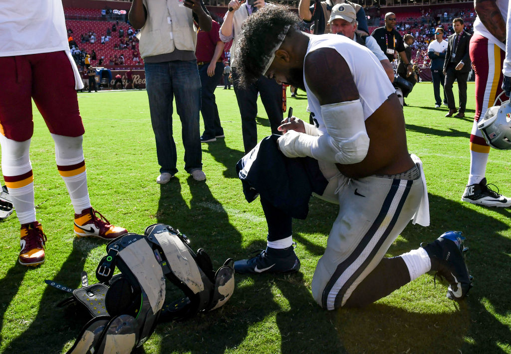 Dallas Cowboys running back Ezekiel Elliott signs his jersey before exchanging it with an opponent