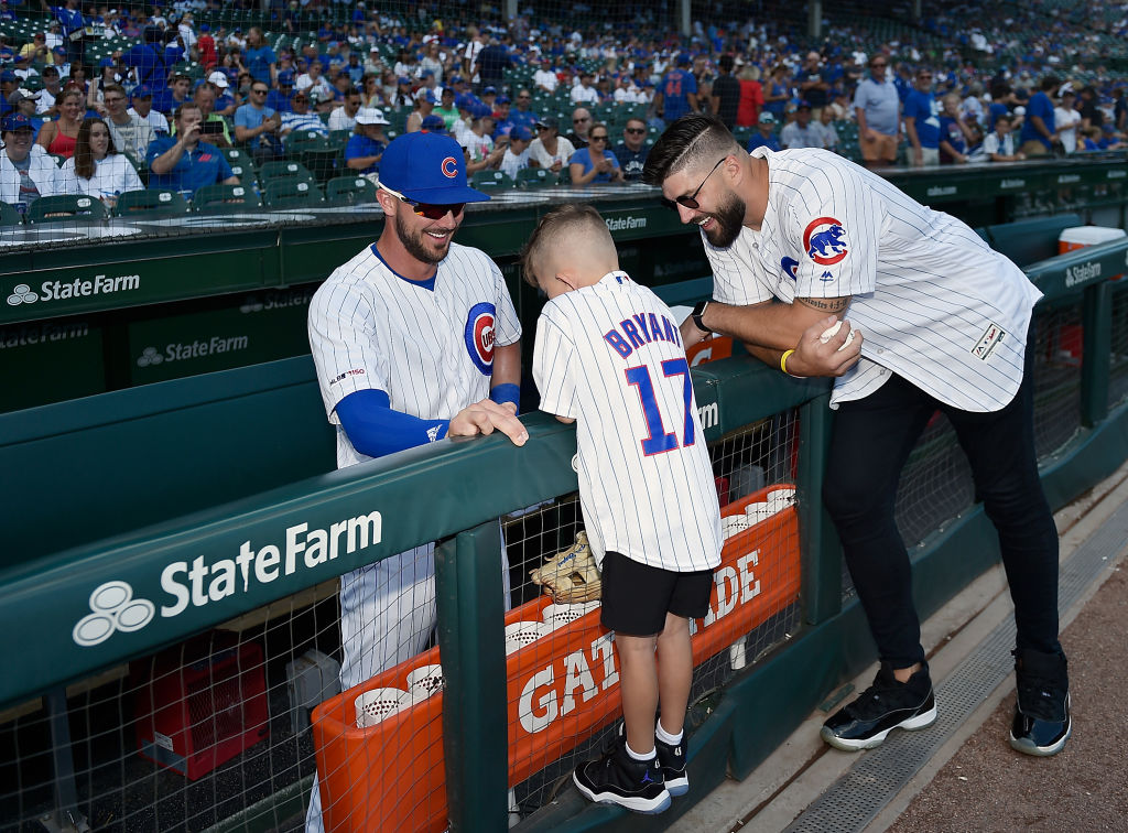 Kashton Miller and his father former Chicago Bears player Zach Miller visits with Kris Bryant of the Chicago Cubs before a game