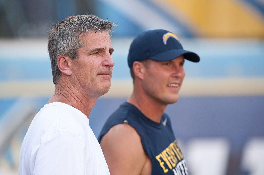 Current Colts head coach Frank Reich and former Chargers quarterback Phillip Rivers watch the field from the sideline.