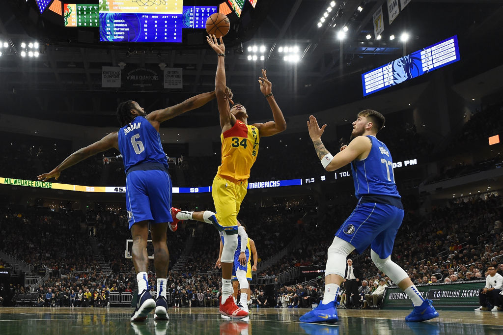 Giannis Antetokounmpo of the Milwaukee Bucks is fouled by DeAndre Jordan of the Dallas Mavericks next to Luka Doncic