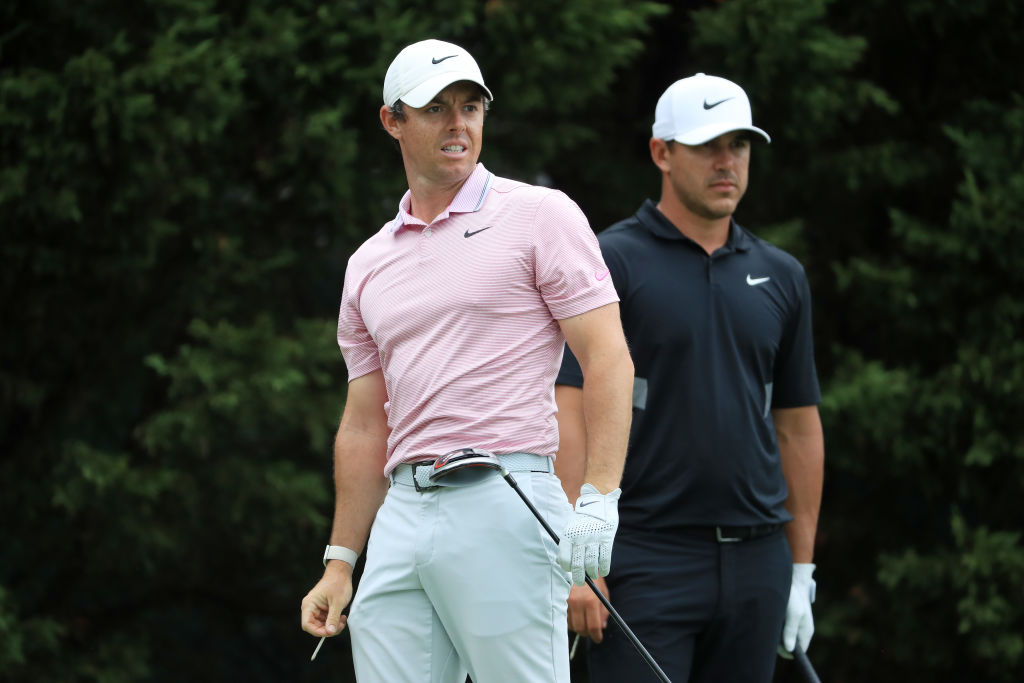 Brooks Koepka and Rory McIlroy look on from the eighth tee