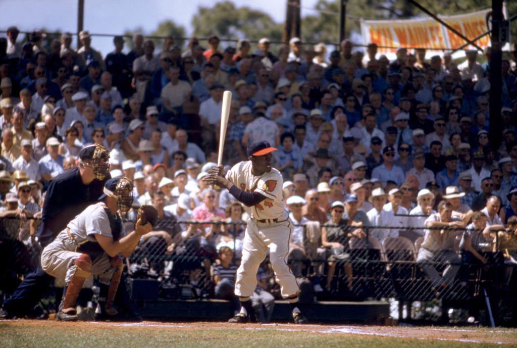 Hank Aaron of the Milwaukee Braves bats during an MLB Spring Training game in 1957