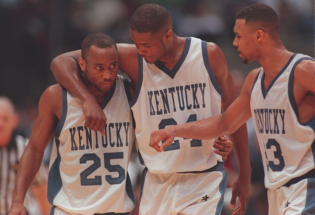 Members of Kuntucky's 1996 Final Four team talk on the court