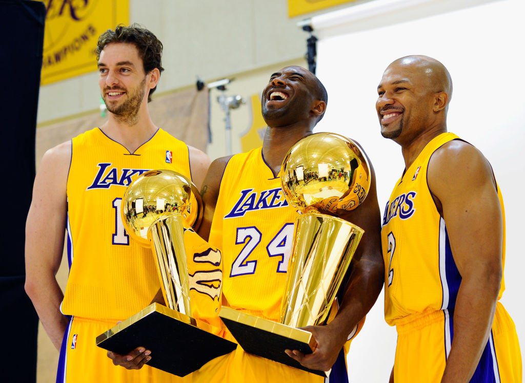 Kobe Bryant and his teammates holding two trophies