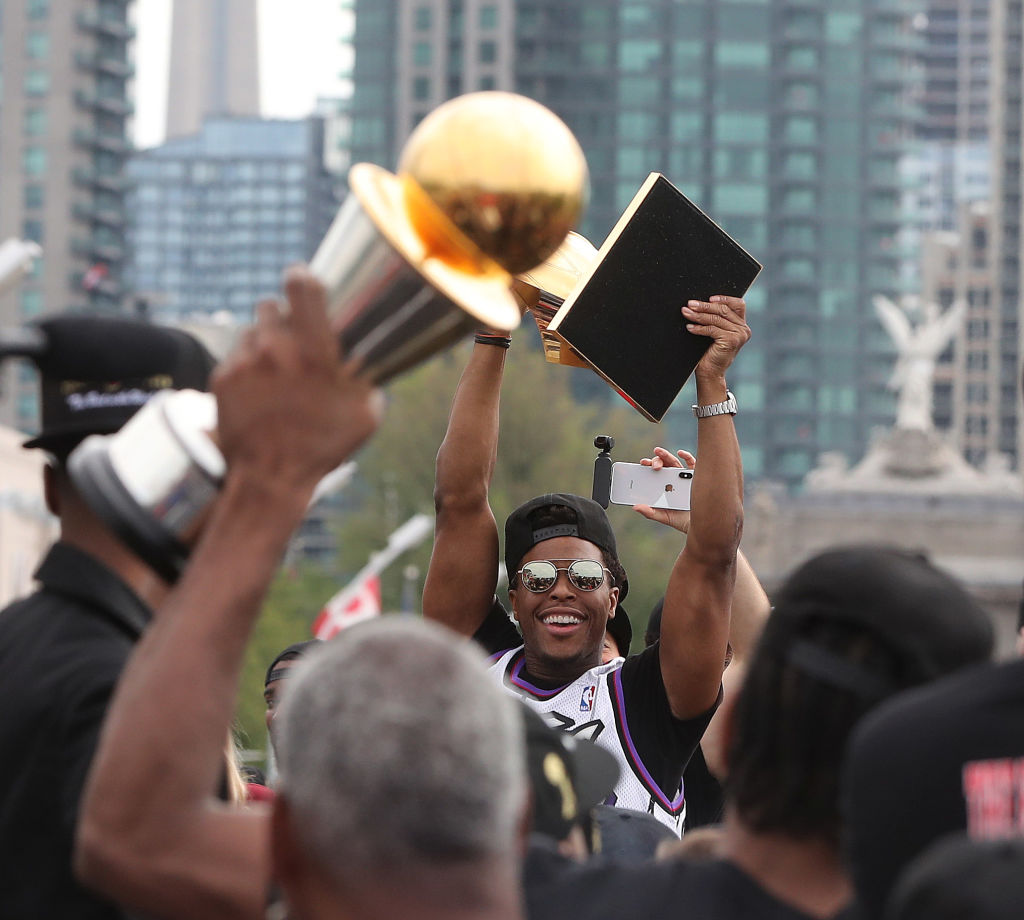 Kyle Lowry hoists the Larry O'Brien NBA Championship Trophy as the Toronto Raptors hold their victory parade in 2019